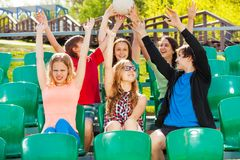 Teens hold ball and cheer for the team at tribune Royalty Free Stock Photo