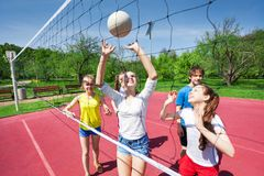 Teens holding arms up and playing volleyball. Near net on the playing court during sunny summer day stock photo