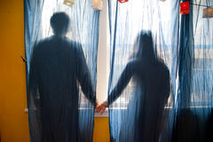Teens holding hands. Young couple holding hands behind blue curtains stock photo