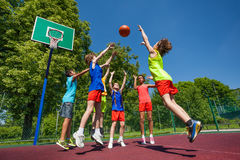 Teens in jump playing basketball game together Royalty Free Stock Photos