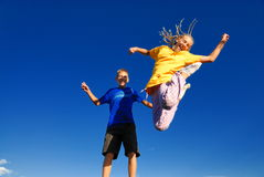 Teens jumping into the air. A picture of a boy and a girl, grinning widely as they jump high into the air Stock Image