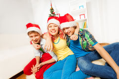 Teens kids on Christmas party in Santa hats Royalty Free Stock Photos