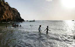Teens and Kids Playing on Water, Ocean Scenery, Black Volcanic Sand Beach, Cape Verde Stock Image