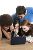 Teens with laptop. Four teenagers of various ethnic backgrounds smile and laugh while looking at a laptop computer together Stock Image