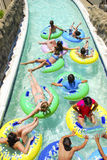 Teens on Lazy River. Teenagers relaxing on flotation inner tubes in lazy river amusement water park area Royalty Free Stock Images