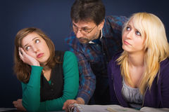 Teens at the lesson. Teacher explaining the lesson to tired and bored schoolgirls Royalty Free Stock Image
