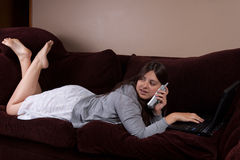 Teens life. Pretty brunette hispanic teenage girl wearing pajamas laying on sofa or couch typing on laptop and talking on phone and looking at television stock image