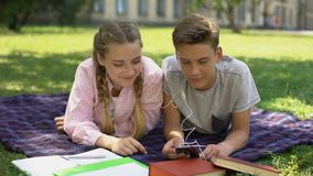 Teens listening to music during homework break, lying on plaid in park, rest. Stock footage stock video footage