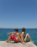 Teens in love. Romance - Boy and girl (teens - best friends) sitting beside the Adriatic sea on the back of each other. Vertical color photo Royalty Free Stock Image