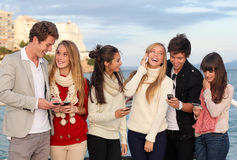 Teens with mobile or cell phones. Group of happy smiling teens, kids, texting and calling with mobile or cell phones Royalty Free Stock Photography