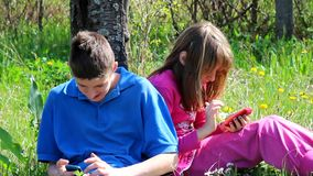 Teens on mobile phones. Teenagers having fun with their mobile phones in nature