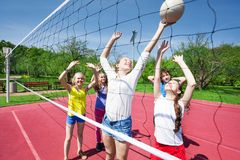 Teens in motion with arms up play volleyball. Near net on the playing court during sunny summer day Royalty Free Stock Images