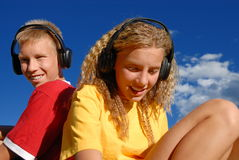Teens with music headphones. A view of a teenage boy and girl, outdoors on a bright sunny day, listening to their favorite music on headphones.  Blue sky and Stock Photos