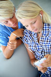 Teens music time. Teenagers using smartphone with earphones Royalty Free Stock Images