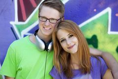 Teens near graffiti wall. Royalty Free Stock Image