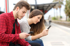 Teens obsessed with smart phones in a train station Royalty Free Stock Photography