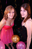 Teens at party. Two pretty teen girls in party dresses with confetti and balloons Stock Photos