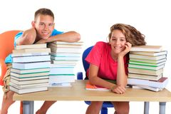 Teens with piles of books. Two teen siblings sitting at a table with piles of books isolated against a white background Royalty Free Stock Photos