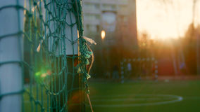 Teens play soccer across football goal at summer evening, de-focused background. Wide angle Stock Photo