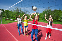 Teens play during volleyball game on playground Royalty Free Stock Images