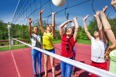 Teens playing actively near the volleyball net Stock Photo