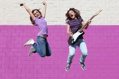 Teens playing guitar jumping Stock Photos