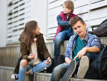 Teens playing on smarthphones and listening to music. Smiling teens playing on smarthphones and listening to music Royalty Free Stock Photography