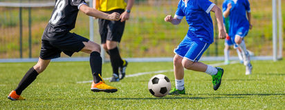 Teens Playing Soccer Football Match. Competition between two youth soccer teams. Boys in blue and black sport uniforms running and kicking soccer ball on a pitch Royalty Free Stock Image