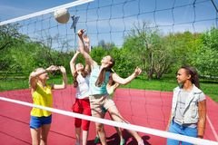 Teens are playing volleyball together on the court Stock Photo