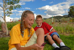 Teens with Ppones outdoors. Two smiling teenagers, one boy and one girl, using cell phones outdoors while sitting in a rural setting Royalty Free Stock Photography