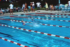 Teens practicing swimming for a swim meet stock image