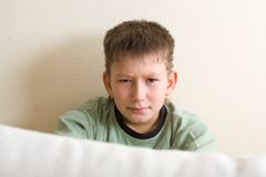 Teens problem. Sad young teenager. Sitting close to the wall and look out from the sofa Royalty Free Stock Image