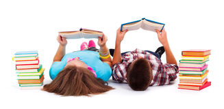 Teens reading books. Teens with books next to them laying on the floor and reading Royalty Free Stock Photos