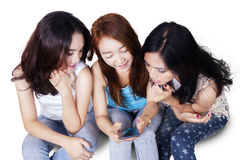 Teens reading message together on cellphone Stock Photography