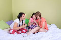 Teens reading text messages. Three pretty teenage girls react surprised or shocked by reading a text message from a mobile phone Stock Photography