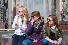 Teens relaxing against a city fountain Stock Images