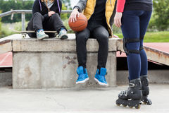 Teens relaxing in skatepark Stock Photo