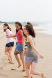 Teens running. Young group of teens running on beach and having fun Stock Photos