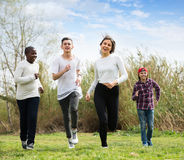 Teens running in spring park. Two girls and two boys running in spring park and smiling Royalty Free Stock Photography
