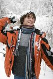Teens  in scarf with snowball. Pretty  European teens boy in scarf with snowball are laughing in winter outdoors Stock Photo