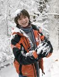 Teens in scarf with snowball. Pretty  European teens boy in scarf with snowball are laughing in winter outdoors Royalty Free Stock Photo