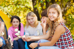 Teens sit on campsite with marshmallow sticks Stock Photo