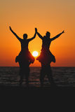 Teens sitting on shoulders of friends in sunset. Silhouette teens sitting on shoulders of friends in sunset Royalty Free Stock Images