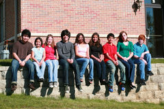 Teens sitting on stone wall. Diverse group of kids sitting on stone wall Stock Images