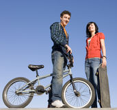 Teens at skatepark. Teens with a bike and skateboard hang out at the skate park Stock Images