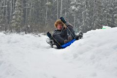 Teens sledding on a saucer Royalty Free Stock Photography