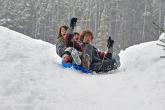 Teens sledding on a saucer Royalty Free Stock Images