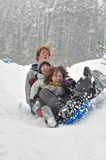 Teens sledding on a saucer Royalty Free Stock Photos