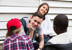 Teens spending time together in sunny day. Happy teens spending time together and talking in sunny day Stock Photo