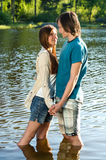 Teens standing in water and holding hands. Romantic teens standing in water and holding hands royalty free stock photos